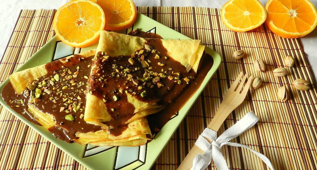 Crespelle all'arancia con salsa al cioccolato e pistacchi